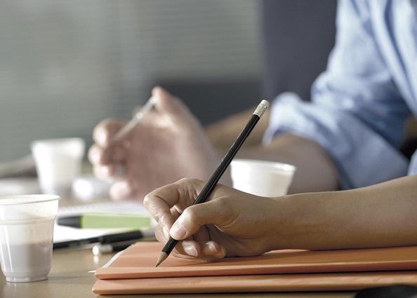 Während eines Meetings macht ein Freelancer Notizen in seinem Notizbuch.